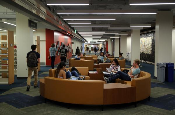 Image of the inside of the library, mountain side, with students walking and sitting on circular couches